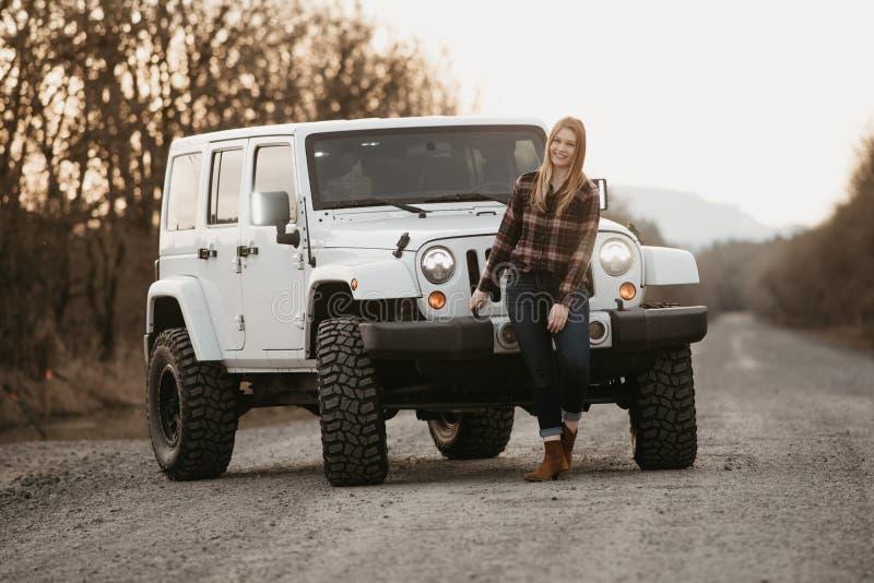 有她的SUV的年轻女人在一条空的石渣路 免版税库存图片