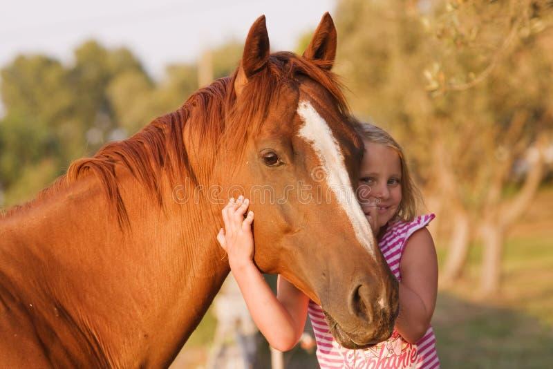 有她英俊的马的逗人喜爱的smilling的小女孩 免版税库存照片