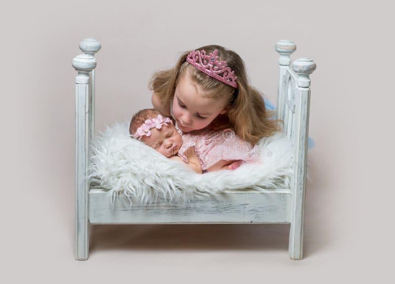 有她逗人喜爱的新出生的睡觉的姐妹的小女孩 库存照片