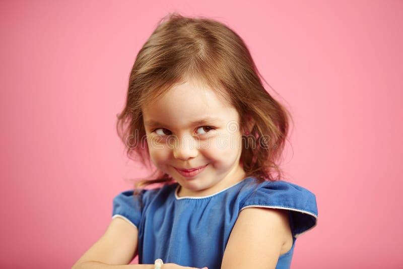 有好奇神色的狡猾女孩看对边和密谋某事 免版税库存照片