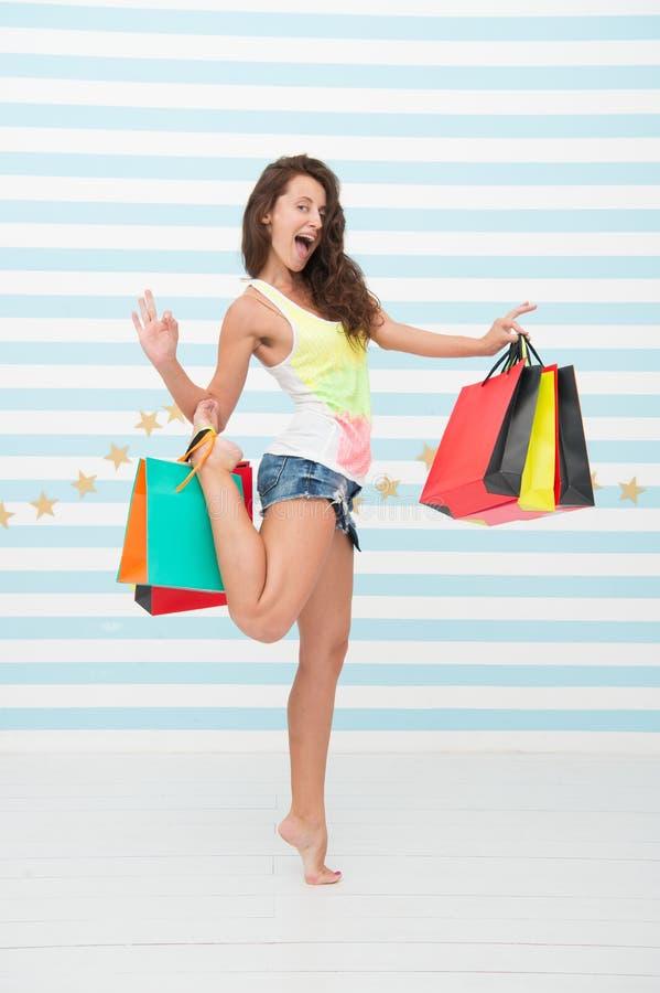 有好姿态的愉快的女售货员 最佳的采购 有购买的愉快的女孩在黑星期五销售以后的购物袋 免版税库存图片
