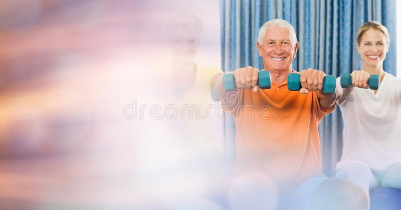 有妇女举的哑铃的老人在健身房 免版税库存图片