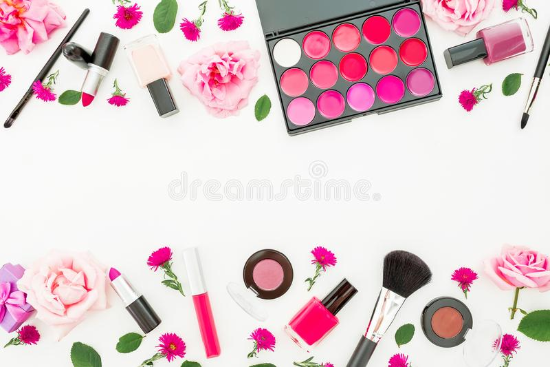 有妇女化妆用品和桃红色玫瑰的女性书桌在白色背景 平的位置,顶视图 秀丽妇女的边界框架 免版税库存图片