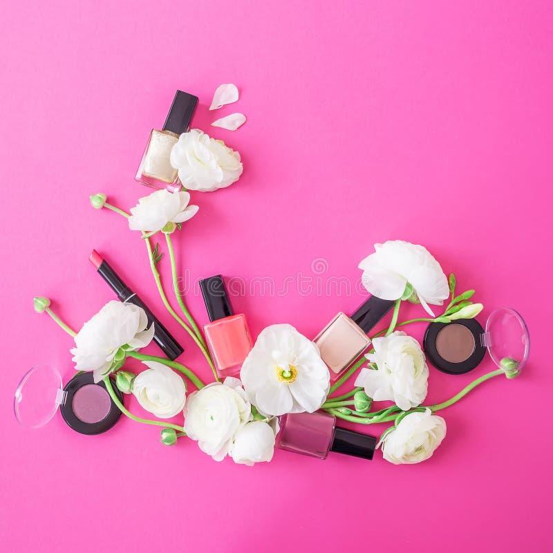 有妇女化妆用品和白花的女性书桌在桃红色背景 平的位置,顶视图 秀丽背景 免版税库存照片