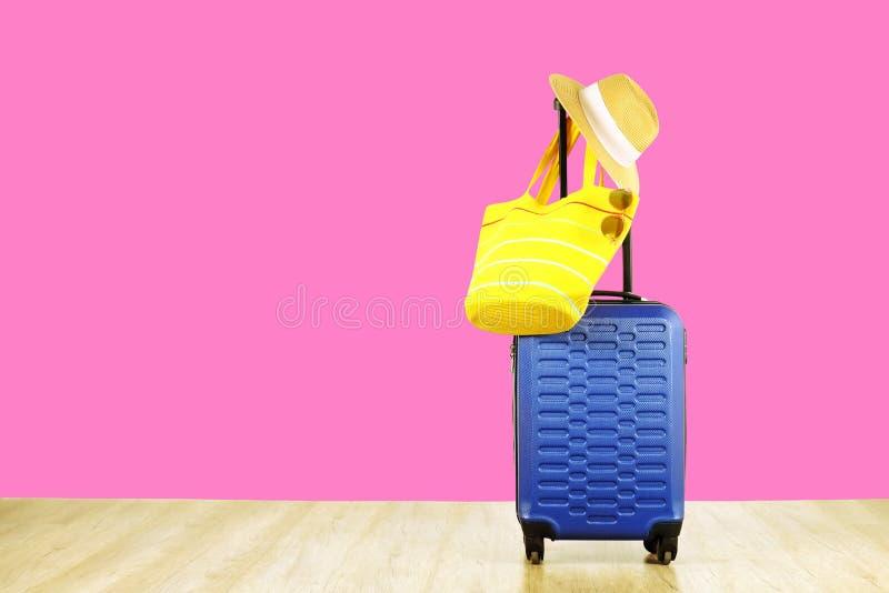 有妇女垂悬在延长的望远镜把柄,黄色海滩袋子,太阳镜的` s草帽的唯一蓝色塑料坚硬壳行李 免版税库存照片