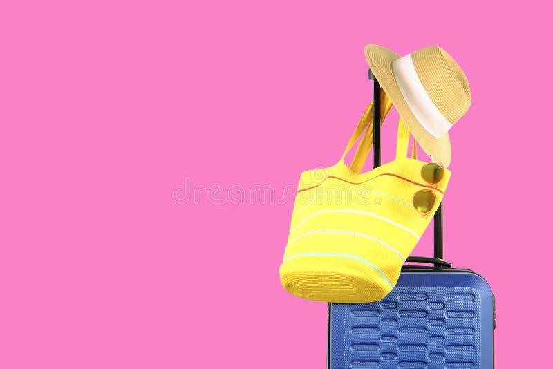 有妇女垂悬在延长的望远镜把柄,黄色海滩袋子,太阳镜的` s草帽的唯一蓝色塑料坚硬壳行李 免版税图库摄影