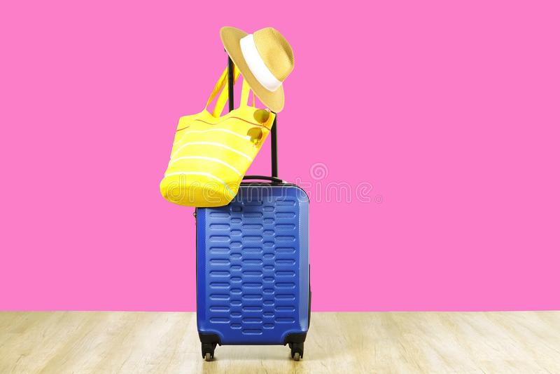 有妇女垂悬在延长的望远镜把柄,黄色海滩袋子,太阳镜的` s草帽的唯一蓝色塑料坚硬壳行李 免版税库存图片