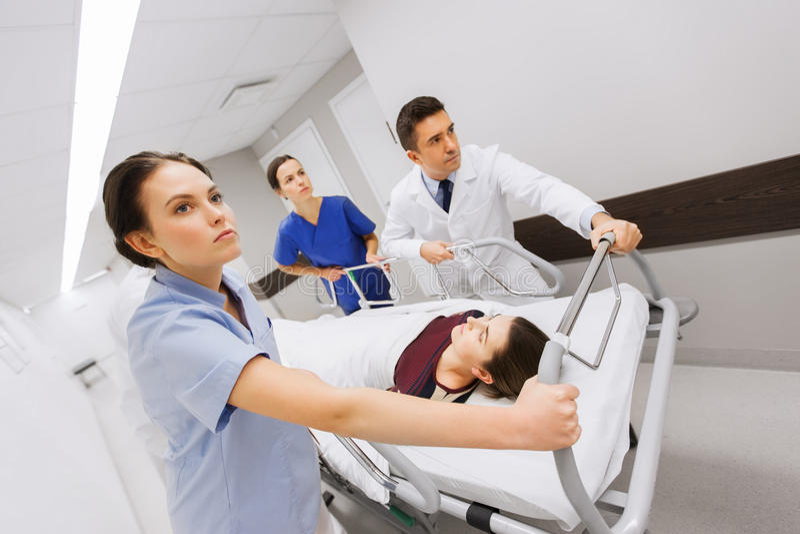 有妇女的军医在紧急状态的医院盖尼式床的 库存图片