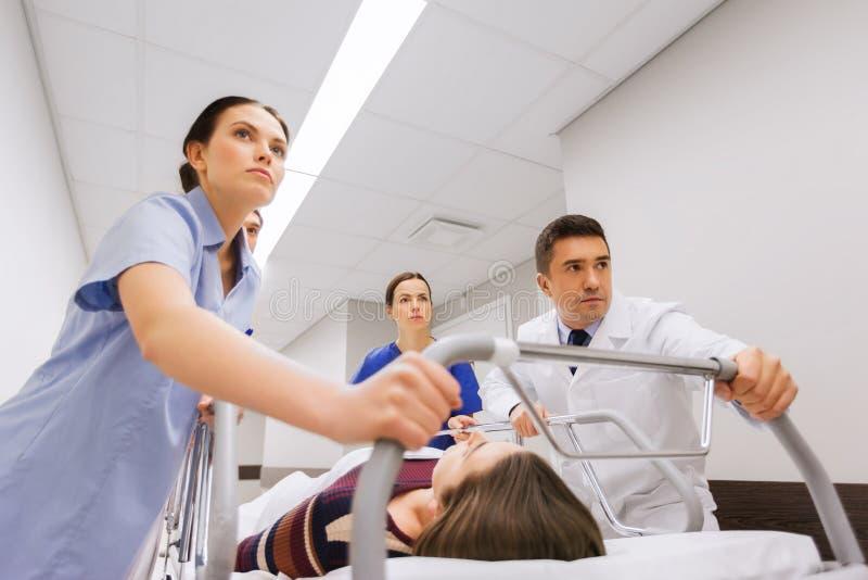 有妇女的军医在紧急状态的医院盖尼式床的 库存照片