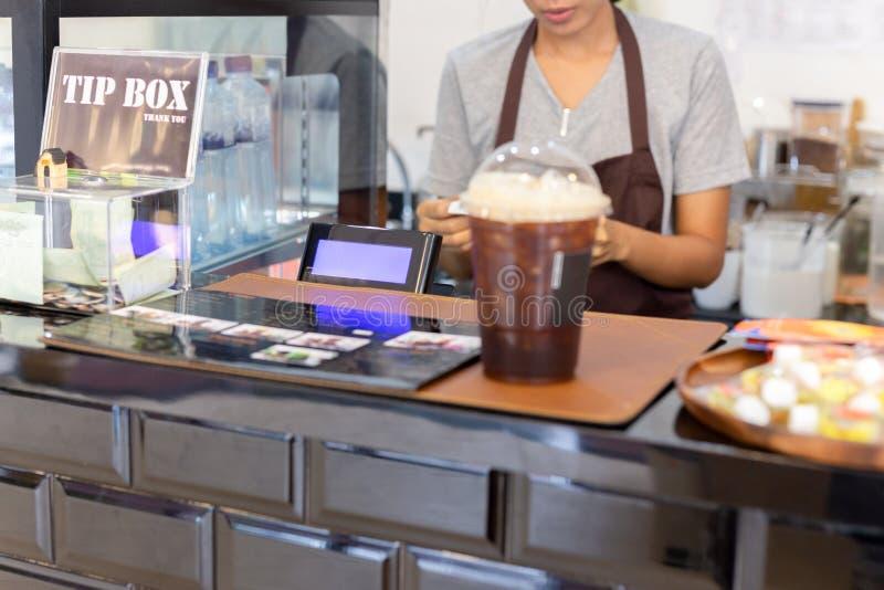 有妇女barista工作的选择的焦点收款机在逆酒吧后 免版税库存照片