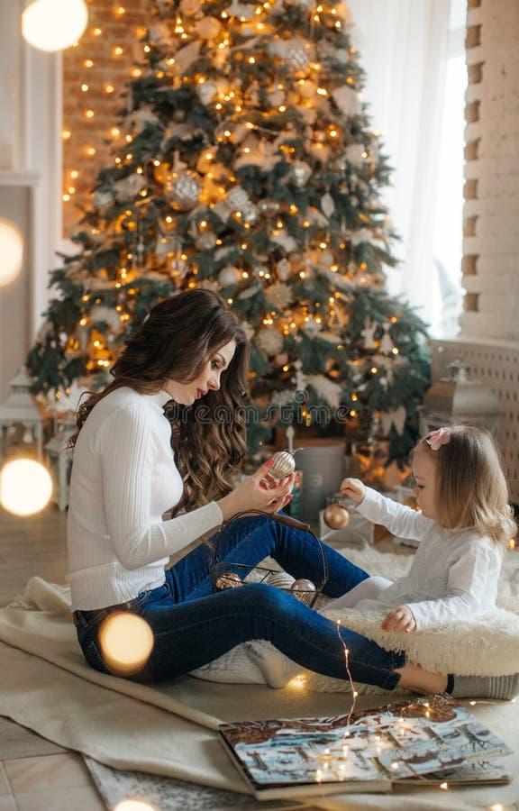 有妈妈的愉快的女孩在新年的风景中 免版税库存照片