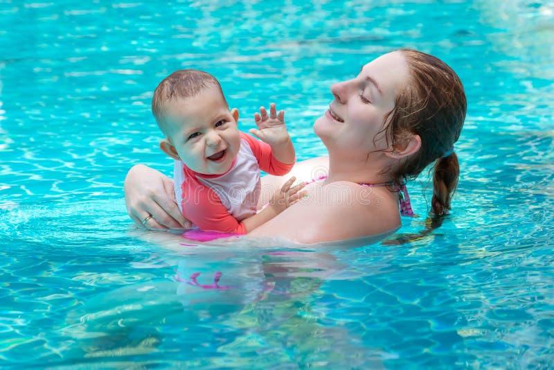 有妈妈的愉快的小孩,被铭记的第一次在一个大水池和非常 非常愉快和欢乐 图库摄影