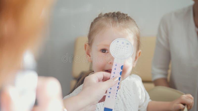 有妈妈的逗人喜爱的白肤金发的女孩在儿童` s眼科学-验光师诊断眼力方面 免版税库存照片