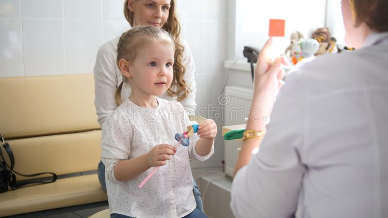 有妈妈的逗人喜爱的白肤金发的女孩在儿童` s眼科学-验光师诊断眼力方面 库存图片
