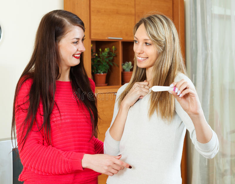 有妊娠试验的愉快的女朋友 库存照片