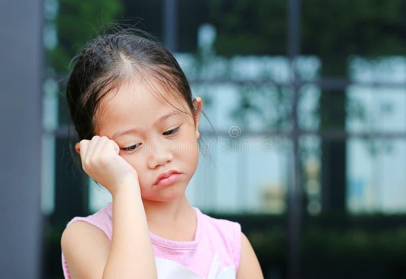 有姿势的不快乐的小孩女孩她的在面颊的手 库存图片