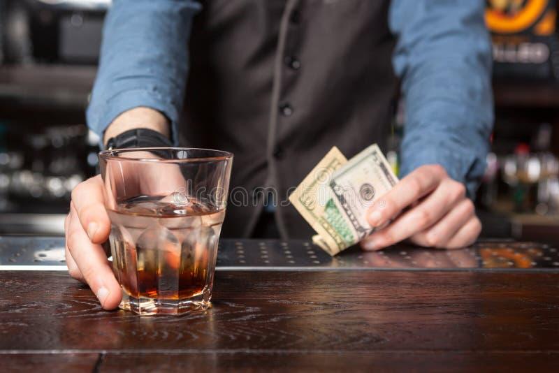 有威士忌酒玻璃和金钱的男服务员在他的手上 免版税库存照片
