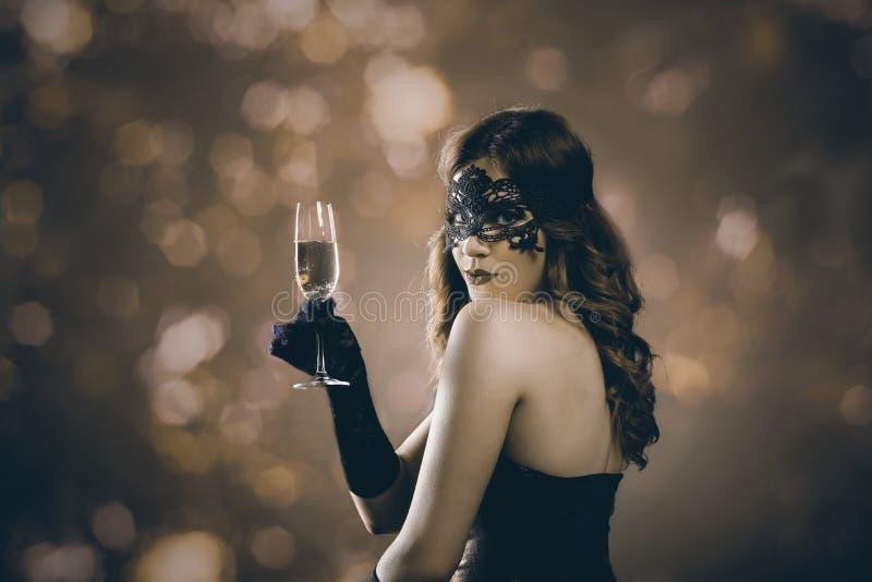 有威尼斯式面具和香槟的夫人 库存照片