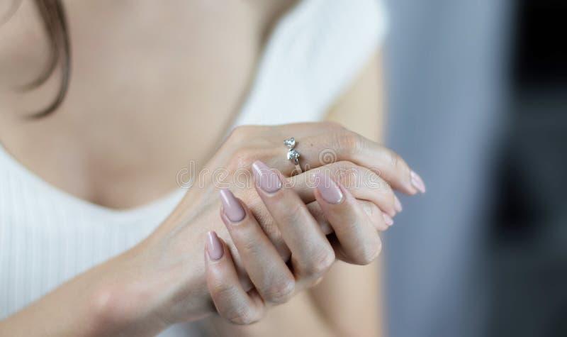 有婚姻请求圆环的妇女的手 有修指甲的年轻女人 库存图片