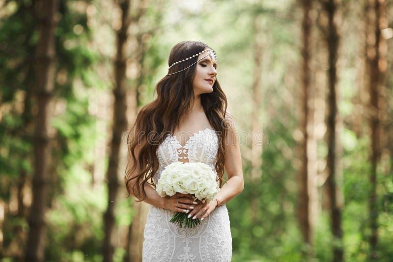 有婚礼发型的典雅的深色的式样妇女与在鞋带礼服的首饰在她的手上的拿着一花束 免版税库存照片