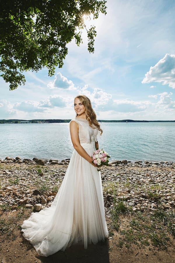 有婚礼发型的和有鲜花花束的在她的手上走由海岸的美丽的年轻愉快的新娘 库存图片