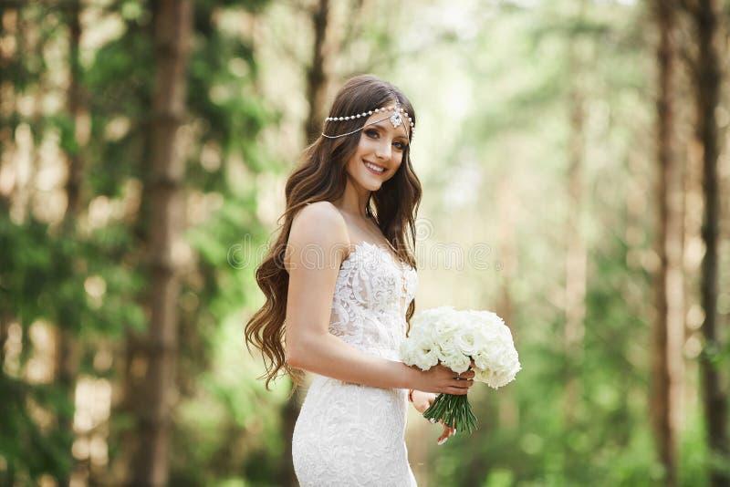 有婚礼发型的美丽的年轻新娘与在鞋带礼服的首饰在她的手上的拿着一花束和 免版税库存图片