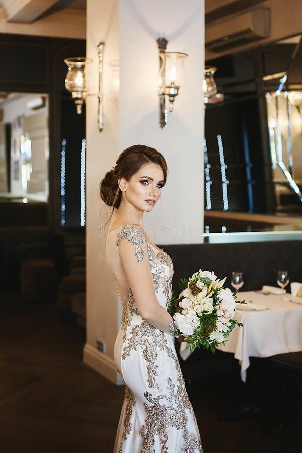 有婚礼发型的美丽的深色的年轻模型妇女和在长的时兴的晚礼服的蓝眼睛对负 库存图片