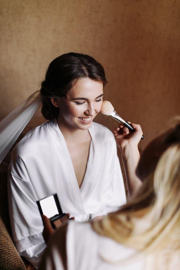 有婚礼构成和发型的美丽的愉快的微笑新娘在卧室,婚姻的新婚佳偶妇女最后的准备 免版税库存图片