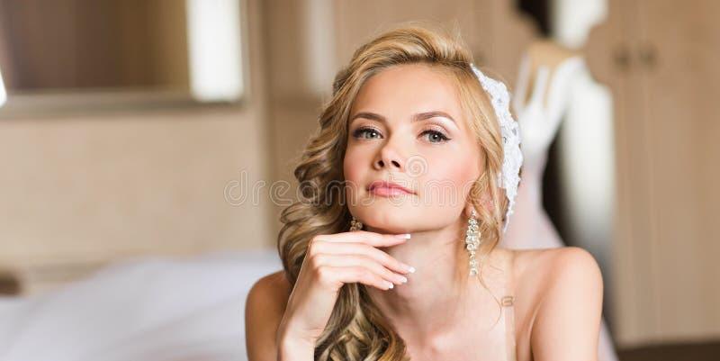 有婚礼构成和发型的美丽的年轻新娘在卧室,可爱的新婚佳偶妇女有最后的准备为 免版税库存图片