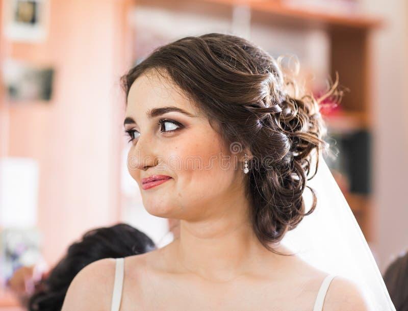 有婚礼构成和发型的美丽的年轻新娘在卧室,婚姻的新婚佳偶妇女最后的准备 愉快 免版税图库摄影