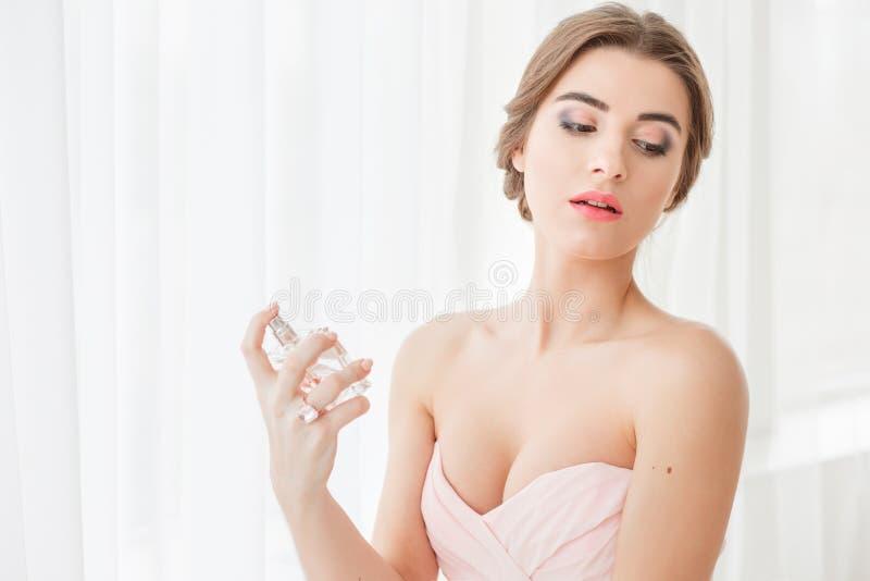 有婚礼构成和发型的美丽的年轻新娘在卧室,婚姻的新婚佳偶妇女最后的准备 愉快 免版税库存照片