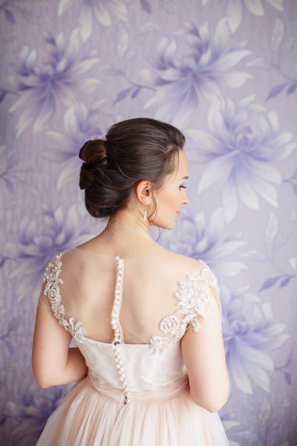 有婚礼构成和发型的美丽的年轻新娘在卧室 与面纱的美丽的新娘画象在她的面孔 特写镜头 免版税库存照片