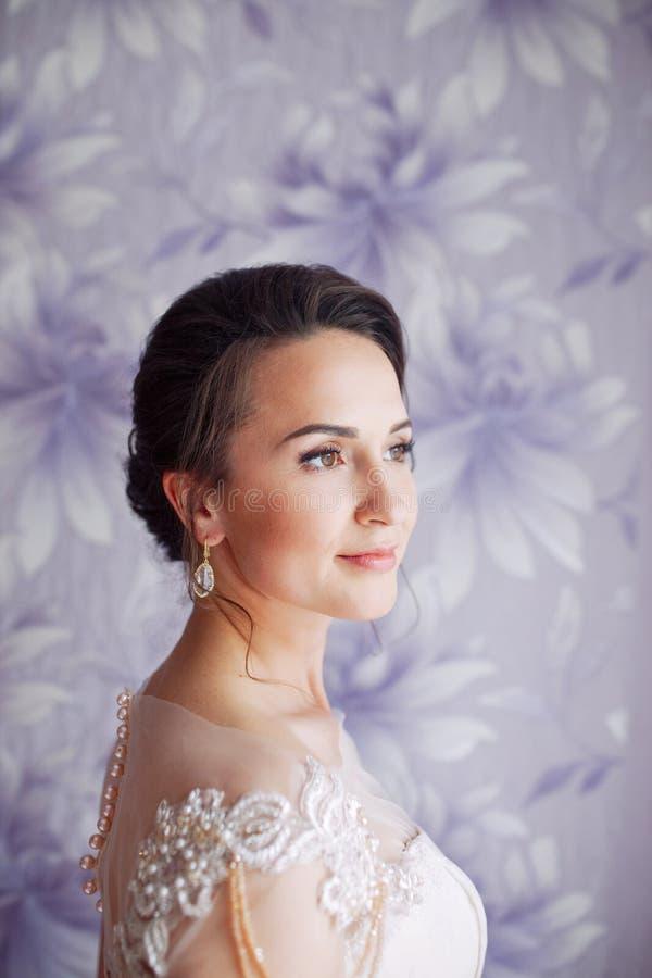 有婚礼构成和发型的美丽的年轻新娘在卧室 与面纱的美丽的新娘画象在她的面孔 特写镜头 库存图片