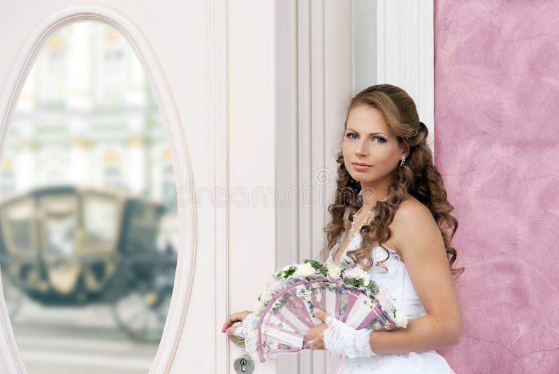 有婚礼爱好者花束的新娘在镜子前 图库摄影