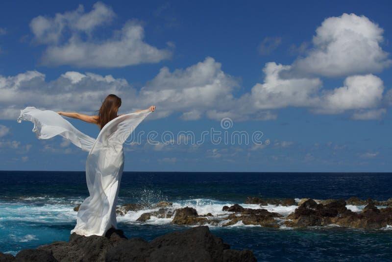 有婚礼礼服白色翼的年轻未婚妻在岩石海岸的在圣地米格尔海岛,亚速尔群岛上 库存照片