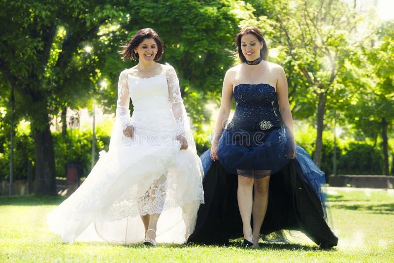 有婚礼礼服的两个妇女新娘和白色走在公园 免版税库存照片