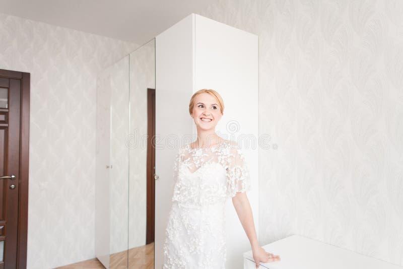 有婚礼花束构成和发型的华美的新娘在家等待新郎的新娘礼服 免版税库存图片