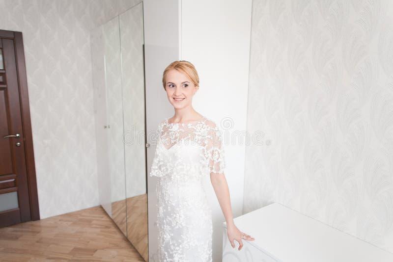 有婚礼花束构成和发型的华美的新娘在家等待新郎的新娘礼服 库存图片