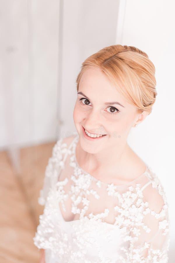 有婚礼花束构成和发型的华美的新娘在家等待新郎的新娘礼服 免版税图库摄影