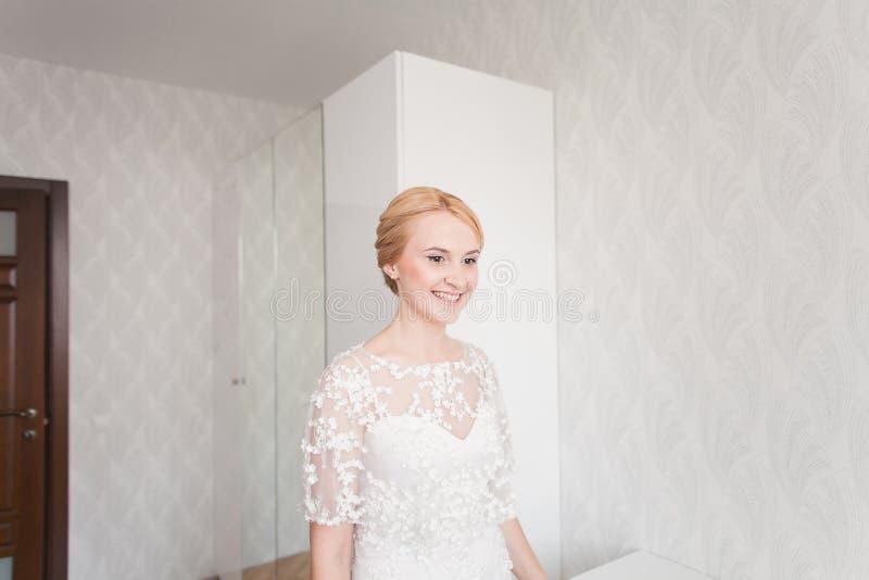 有婚礼花束构成和发型的华美的新娘在家等待新郎的新娘礼服 图库摄影