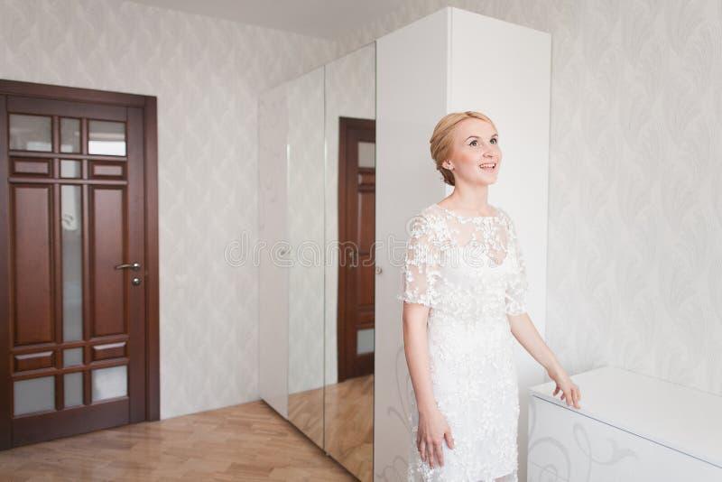有婚礼花束构成和发型的华美的新娘在家等待新郎的新娘礼服 免版税库存照片