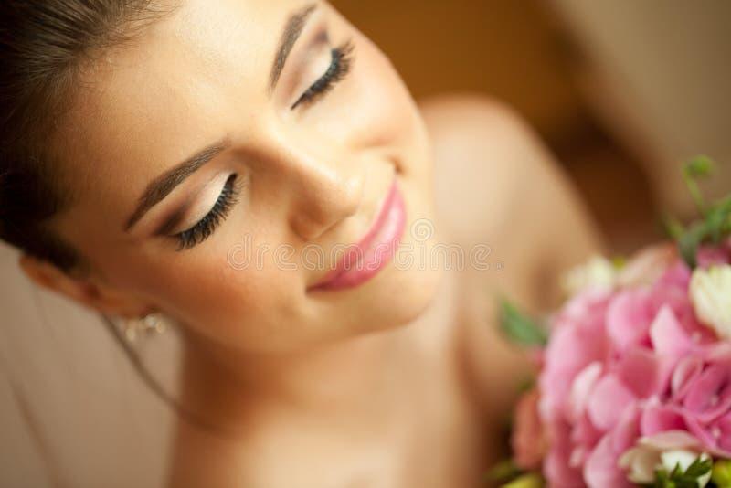 有婚礼花束的美丽的愉快的新娘 免版税库存照片