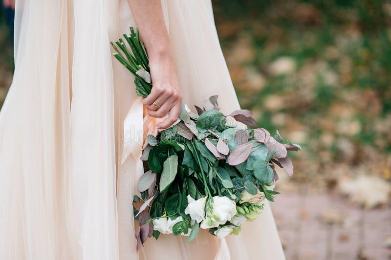 有婚礼花束的美丽的新娘在户外他们的手上在公园 免版税库存图片