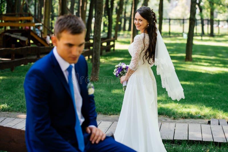 有婚礼花束的美丽的年轻新娘与迷离的新郎在她前面 在爱的韦德夫妇婚礼之日 库存照片