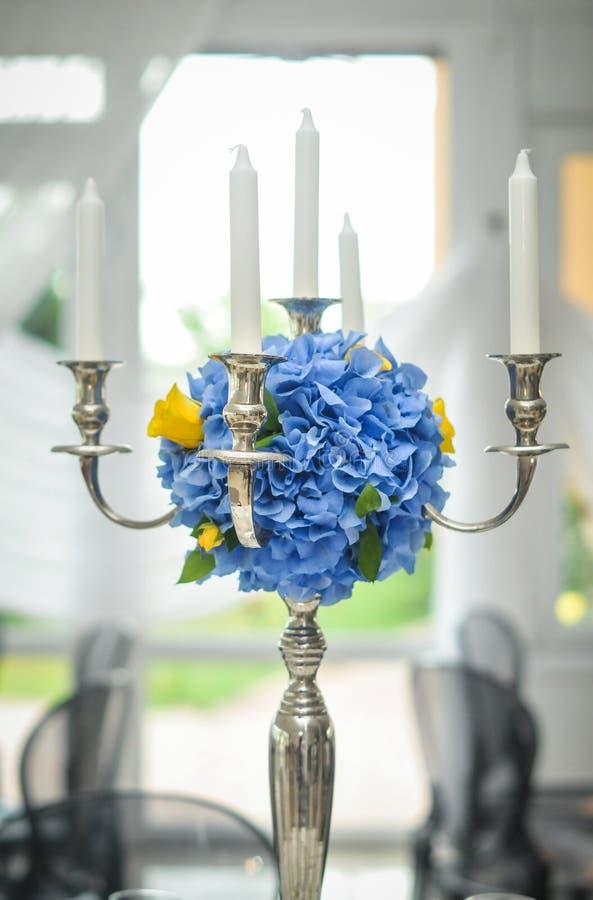 有婚姻花束的蓝色花的古色古香的烛台 有花装饰的婚礼烛台在婚礼前 免版税库存图片