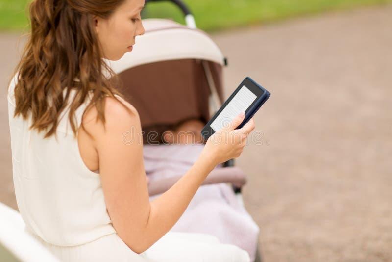 有婴儿推车读书互联网书的母亲在公园 免版税库存图片