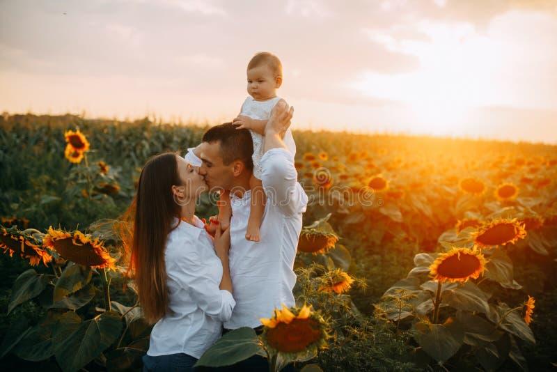 有婴孩亲吻的愉快的年轻父母在向日葵领域 免版税图库摄影