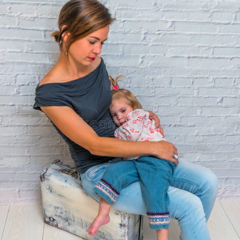 有婴孩的一个母亲在一个手提箱附近对砖墙, gir 免版税库存图片