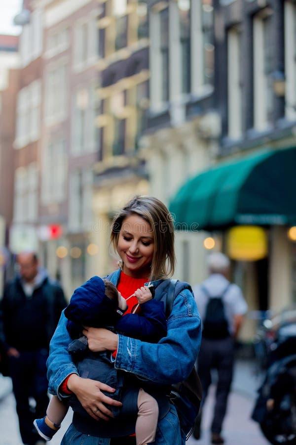 有婴孩的女孩在阿姆斯特丹街道的载体的  图库摄影