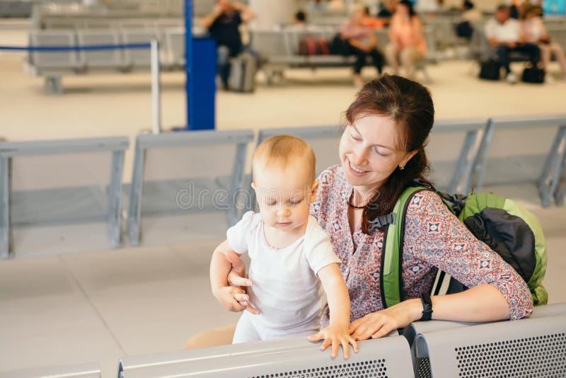 有婴孩的年轻母亲免税的在机场 免版税库存图片